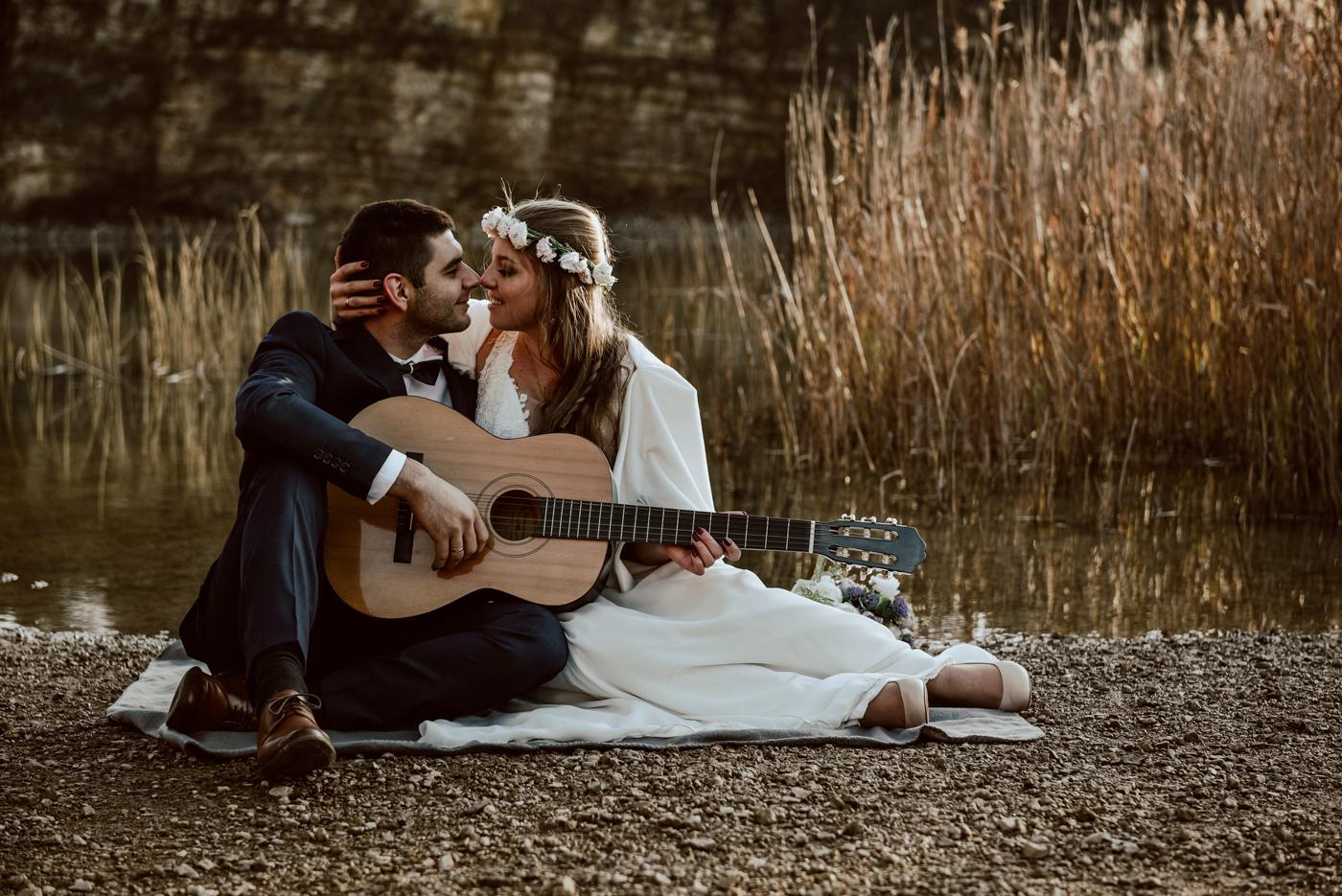 Młoda Para nad wodą z gitarą zaczyna się całować.