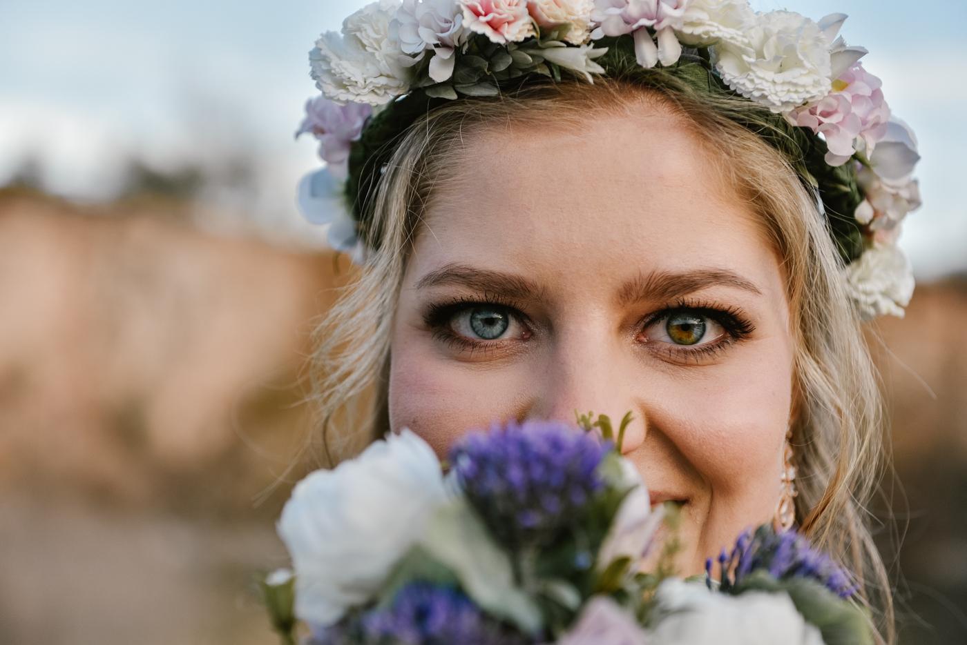 Piękna Panna Młoda z uśmiechem. Na głowie ma wianek a jej oczy są w dwóch kolorach. Jedno oko jest niebieskie a drugie brązowoniebieskie.