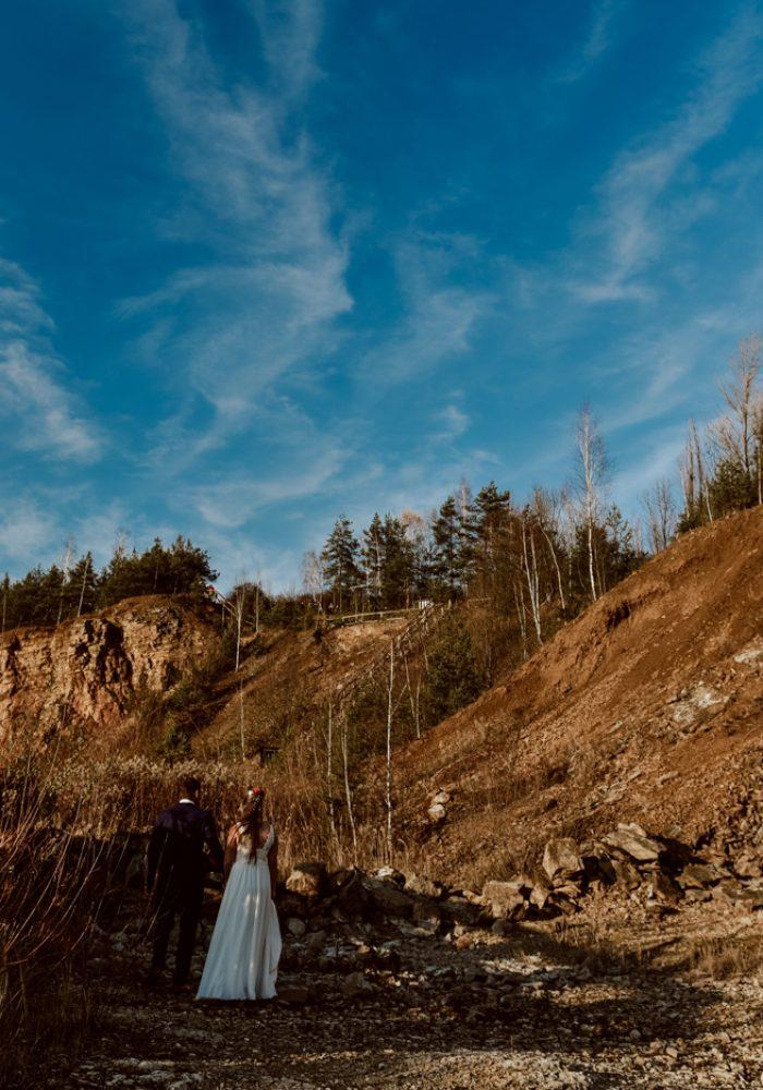 Piękne niebieskie niebo i skałki między którymi przechodzi Młoda Para.